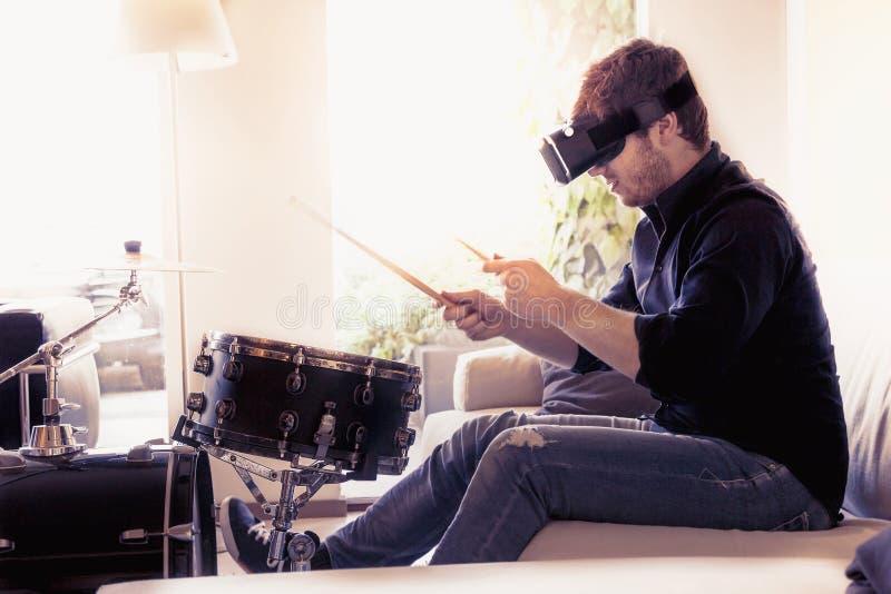Junge erwachsene spielende Trommeln zu Hause unter Verwendung des Zuschauers für virtuelle Realität lizenzfreies stockfoto