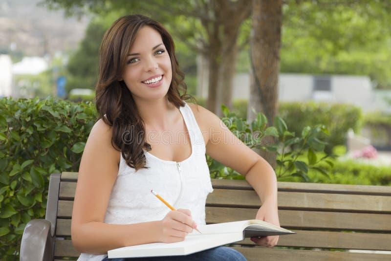 Junge erwachsene Studentin auf Bank draußen stockfotografie
