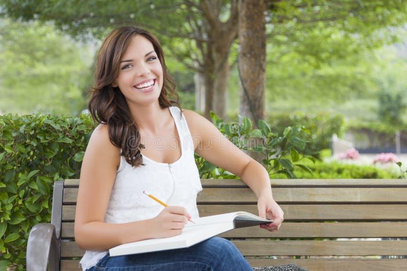 Junge erwachsene Studentin auf Bank draußen lizenzfreie stockfotos