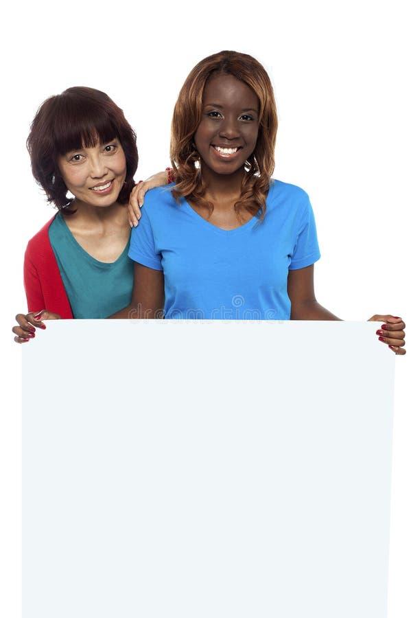 Junge ethnische Freunde hinter unbelegtem Anzeigenvorstand stockfotos