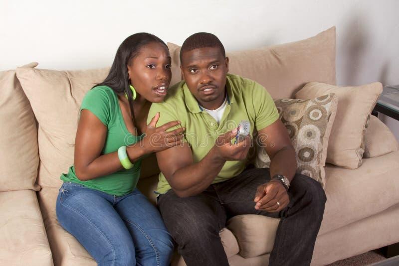 Junge ethnische schwarze Paare mit Fernsteuerungs stockfotografie