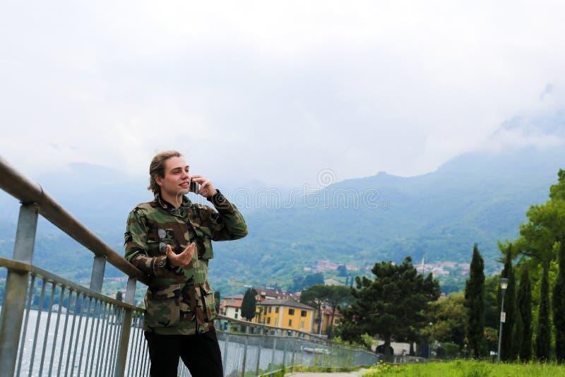 Junge Europäer sprechen mit Smartphone in der Nähe von Banister, See Como und Alpen im Hintergrund lizenzfreie stockfotos