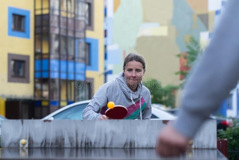 Junge europäische Frau, die Tischtennis im Yard spielt lizenzfreies stockbild