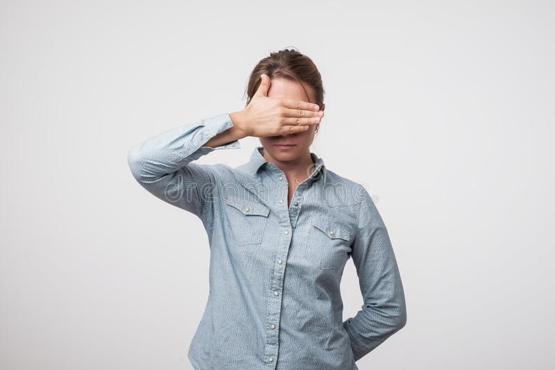 Junge europäische Frau im Hemd versteckt ihr Gesicht, Studiofoto auf einem grauen Hintergrund stockfotos
