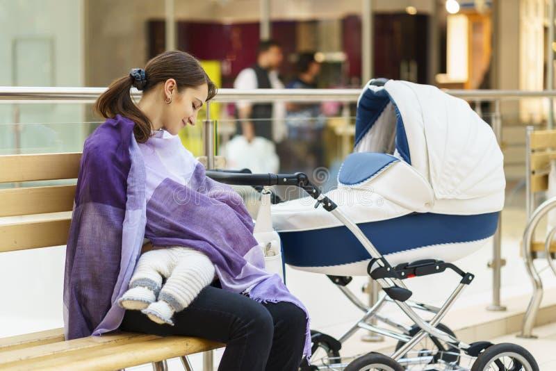 Junge europäische Frau mit violetter Stola stillt ihr kleines Kind nah an weißem Kinderwagen am öffentlichen Ort Einkaufsmal stockfotos