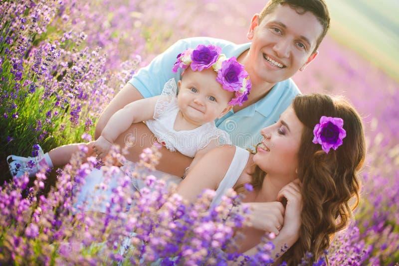 Junge Familie auf einem Lavendelgebiet stockfotos
