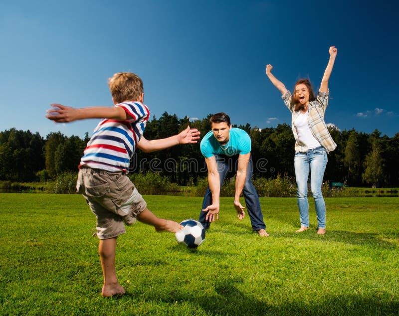 Junge Familie, die Fußball spielt stockfoto