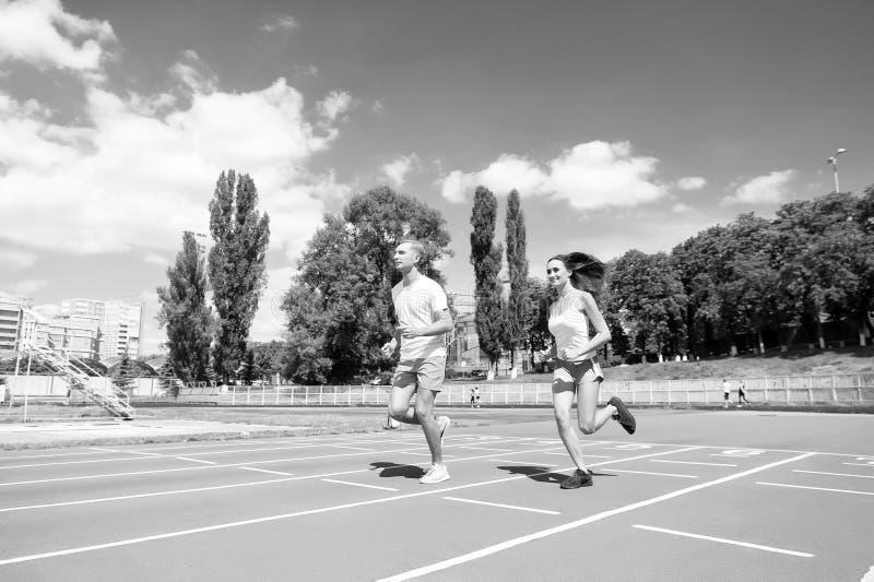Junge Familie, die gesunden Lebensstil fördert Frauen- und Mannlaufstadion Paarläufer, die draußen ausbilden Paare oder Familie stockfotografie