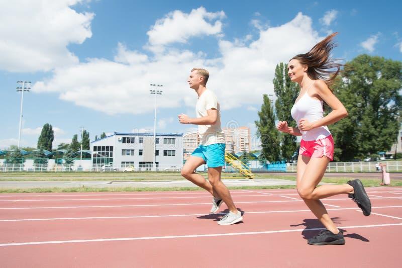 Junge Familie, die gesunden Lebensstil fördert Frauen- und Mannlaufstadion Trainer- und Sportlerbewegungslauftraining vor Rennen stockfotos