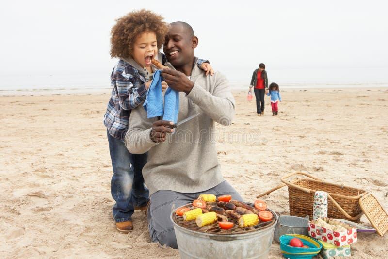 Junge Familie, die Grill auf Strand genießt stockfotografie