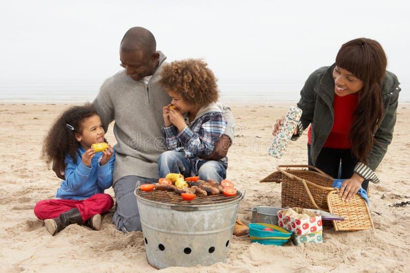 Junge Familie, die Grill auf Strand genießt lizenzfreie stockfotos