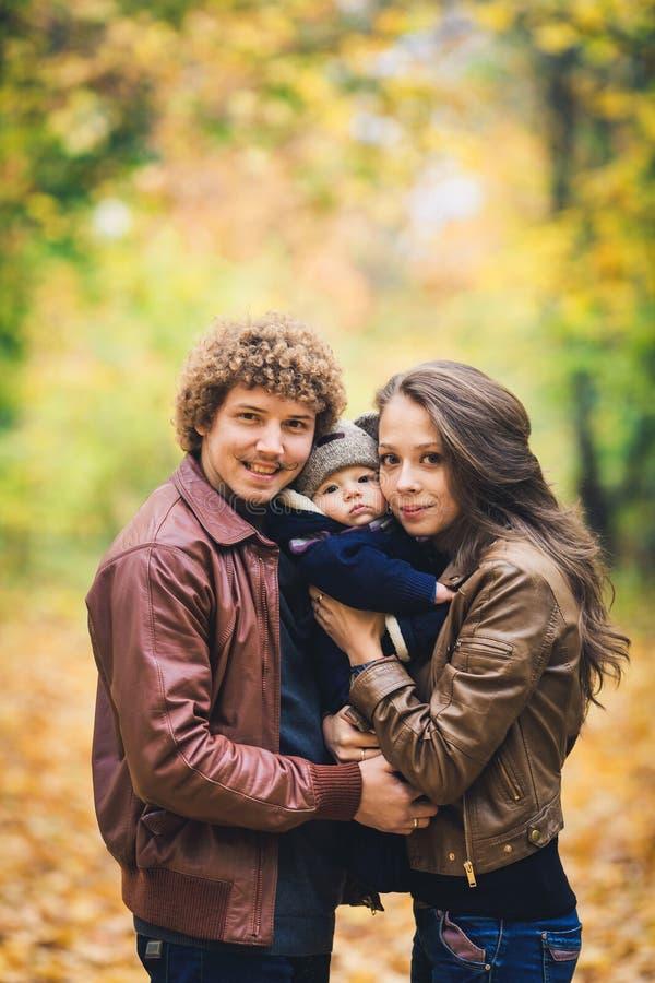 Junge Familie, die im Herbst im Park umarmt lizenzfreie stockbilder
