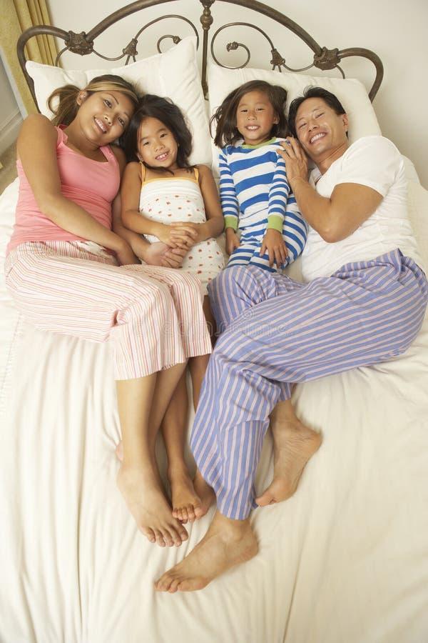 Junge Familie, die im Schlafzimmer sich entspannt stockbilder