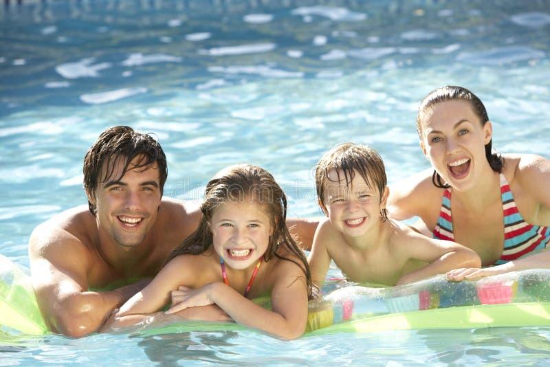 Junge Familie, die im Swimmingpool sich entspannt stockbilder