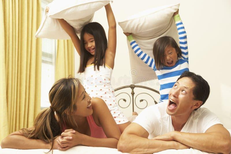 Junge Familie, die Kissen-Kampf hat stockfotos