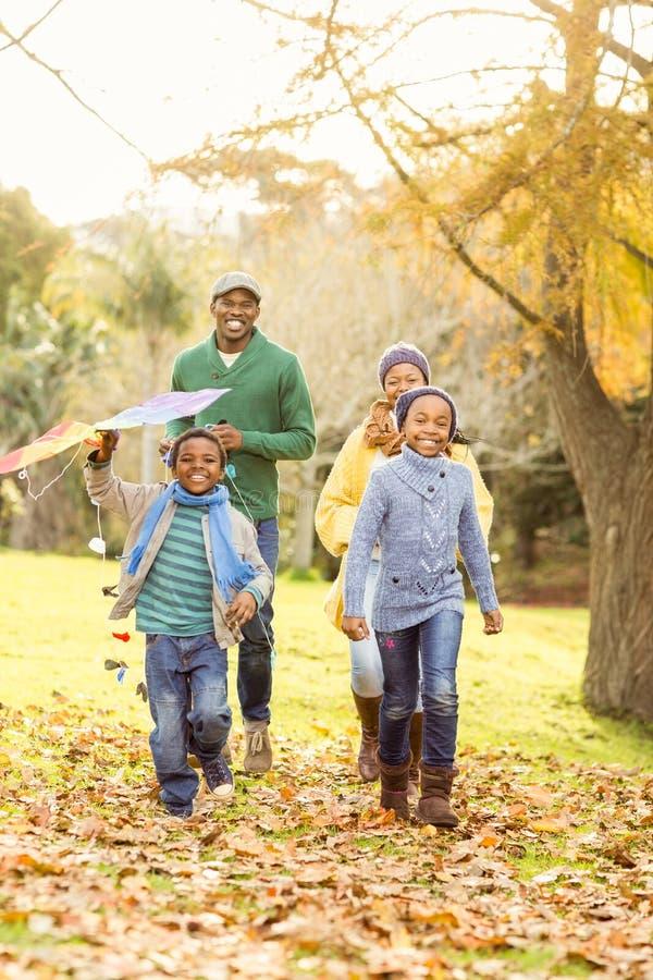 Junge Familie, die mit einem Drachen spielt stockfotografie
