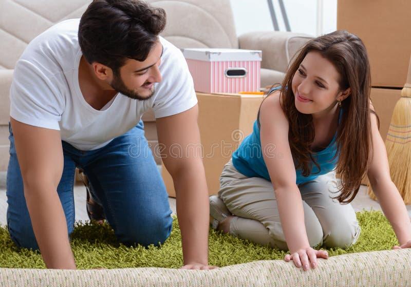 Junge Familie, die am neuen Haus mit K?sten auspackt lizenzfreies stockfoto