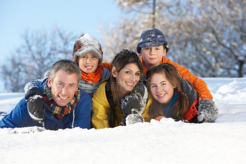 Junge Familie, die Spaß in der Snowy-Landschaft hat stockfotos