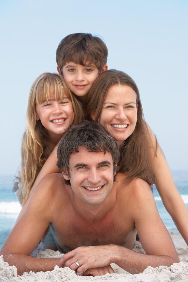Junge Familie, die Spaß am Strand-Feiertag hat lizenzfreie stockfotos
