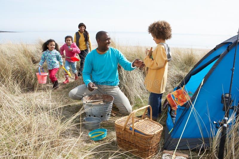 Junge Familie, die an Strand-kampierendem Feiertag sich entspannt lizenzfreies stockbild
