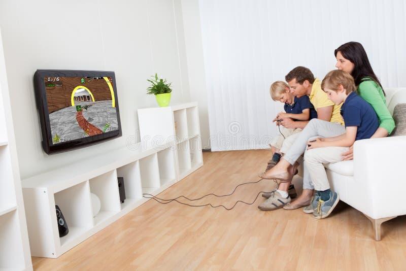 Junge Familie, die Videospiele spielt stockbild