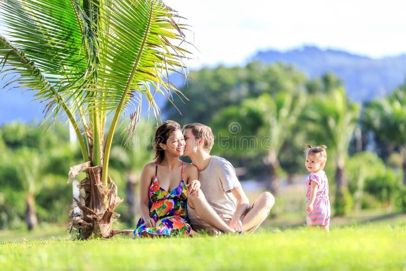Junge Familie, die Zeit in einem tropischen Garten verbringt lizenzfreies stockfoto