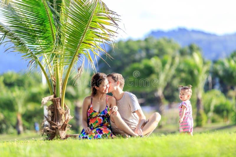 Junge Familie, die Zeit in einem tropischen Garten verbringt lizenzfreie stockfotografie