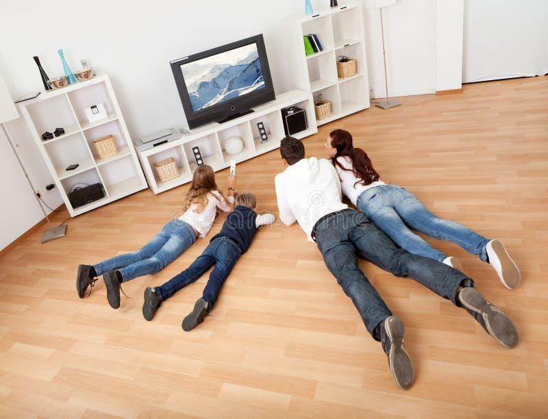Junge Familie, die zu Hause Fernsieht lizenzfreie stockfotografie