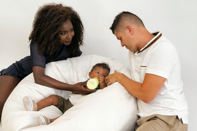 Junge Familie Eltern, die ein Säuglingskind mit Milch einziehen Frauklo stockbild