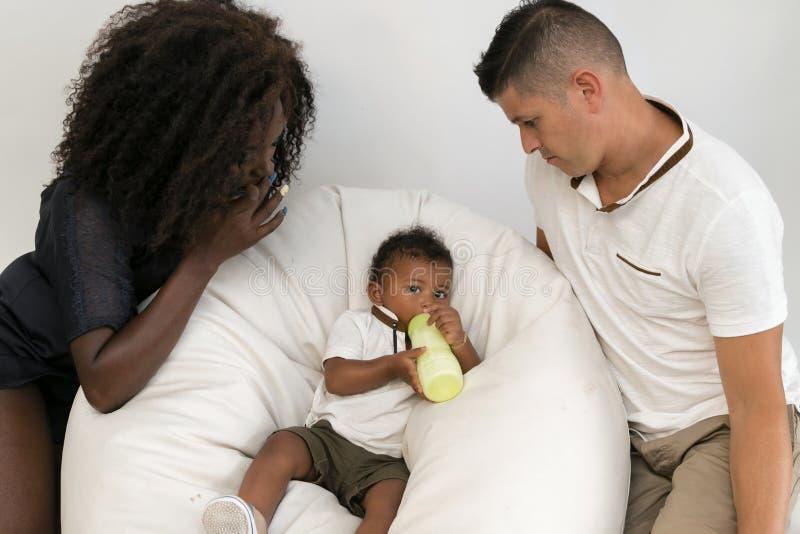 Junge Familie Eltern, die ein Säuglingskind mit Milch einziehen Multi und stockbilder