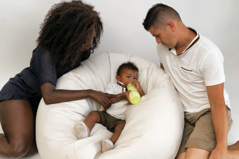 Junge Familie Eltern, die ein Säuglingskind mit Milch einziehen Multi und lizenzfreie stockfotos