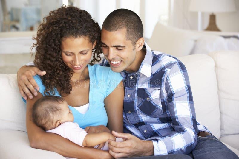 Junge Familie mit dem Baby, das auf Sofa At Home sich entspannt stockfotos