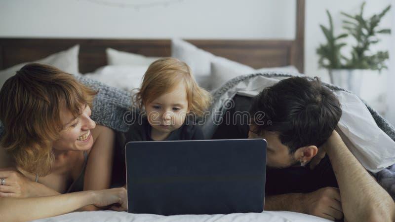 Junge Familie mit dem netten kleinen Mädchen, das mit Tochter während sie aufpassende Laptop-Computer zu Hause liegt im Bett spie stockfotos