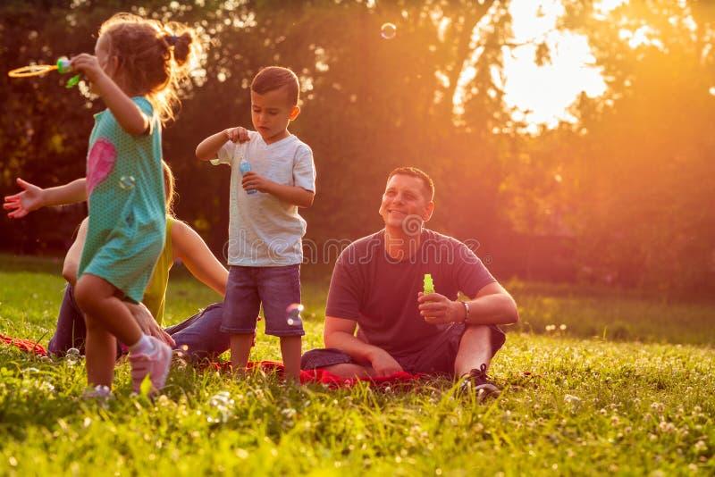 Junge Familie mit den Kindern, die Spaß in der Natur bei Sonnenuntergang haben stockbild
