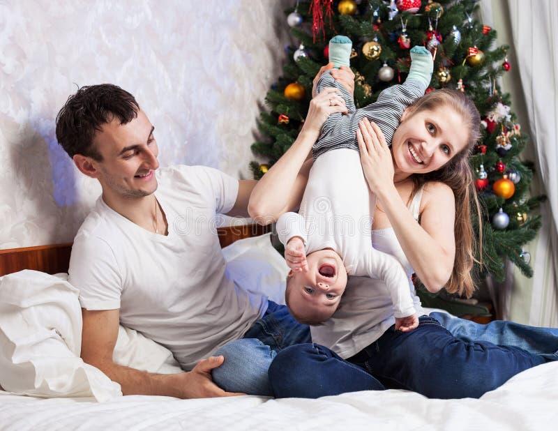 Junge Familie mit einem Baby, das Spaß zu Hause hat stockfoto