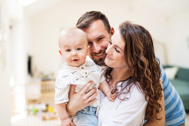 Junge Familie mit einem Baby zu Hause, stehend und werfen für das Foto auf stockfotos