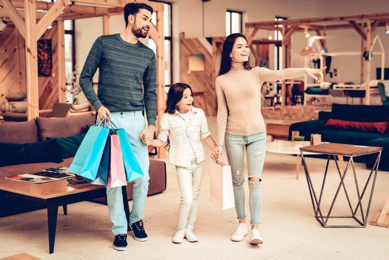 Junge Familie mit Kauf-Taschen Möbelgeschäft stockbilder