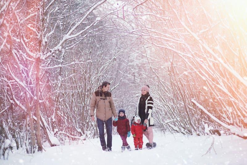 Junge Familie mit Kindern gehen in den Winterpark Winte stockbilder