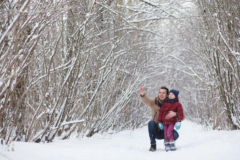 Junge Familie mit Kindern gehen in den Winterpark Winte lizenzfreie stockbilder