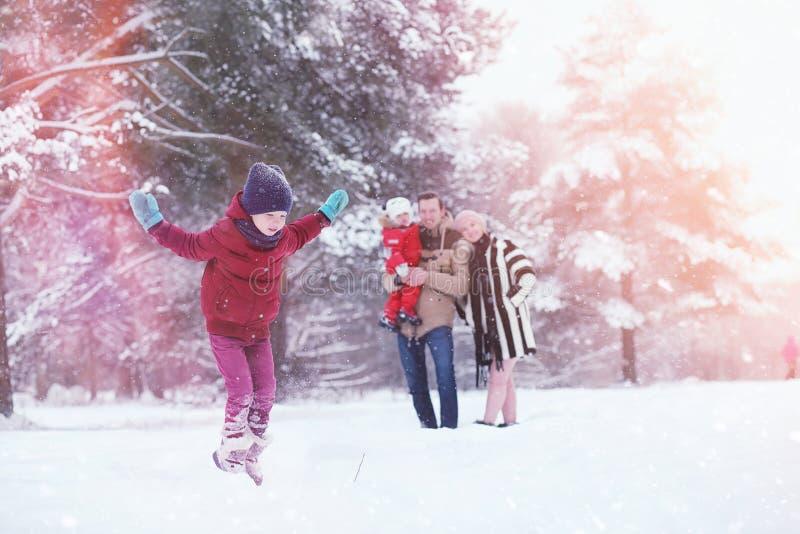 Junge Familie mit Kindern gehen in den Winterpark Winte lizenzfreie stockfotografie