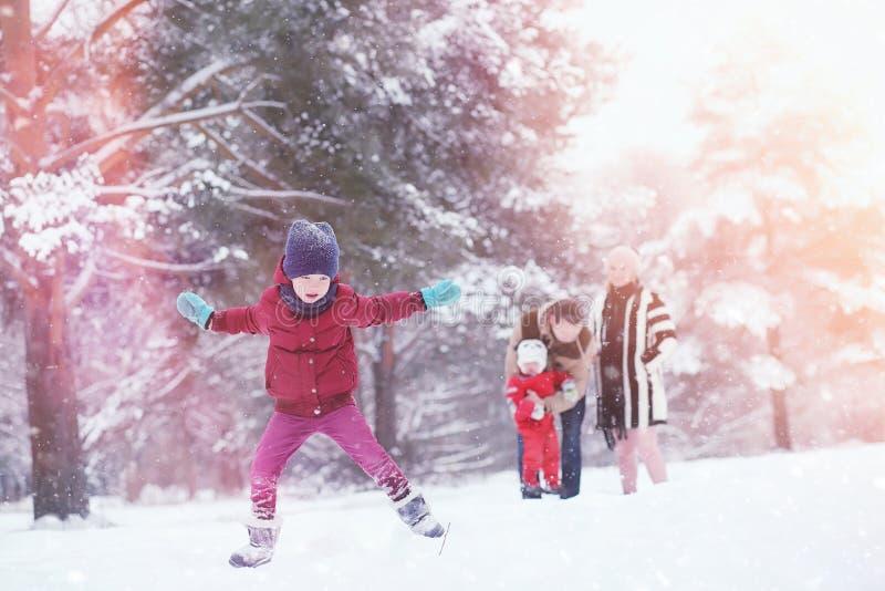Junge Familie mit Kindern gehen in den Winterpark Winte lizenzfreie stockfotos