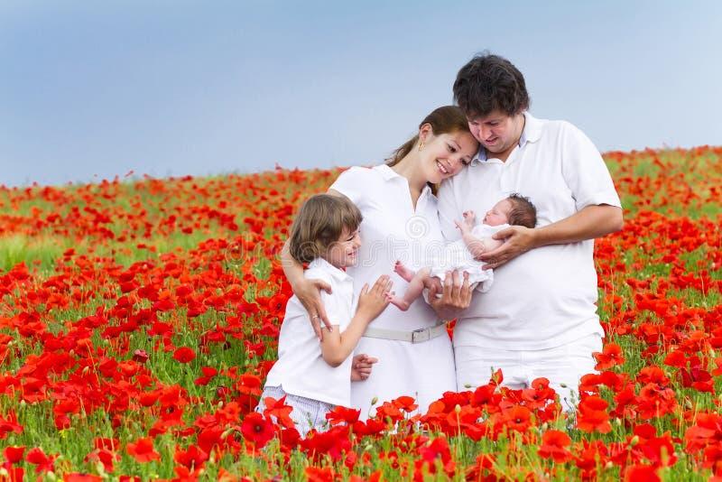 Junge Familie mit zwei Kindern auf einem roten Blumengebiet stockbilder