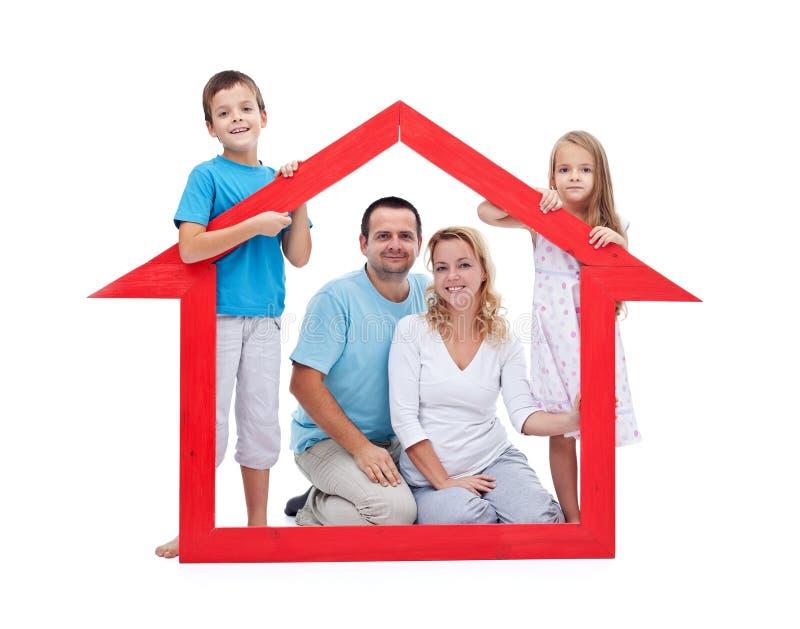 Junge Familie mit zwei Kindern, die Hauszeichen anhalten lizenzfreies stockfoto
