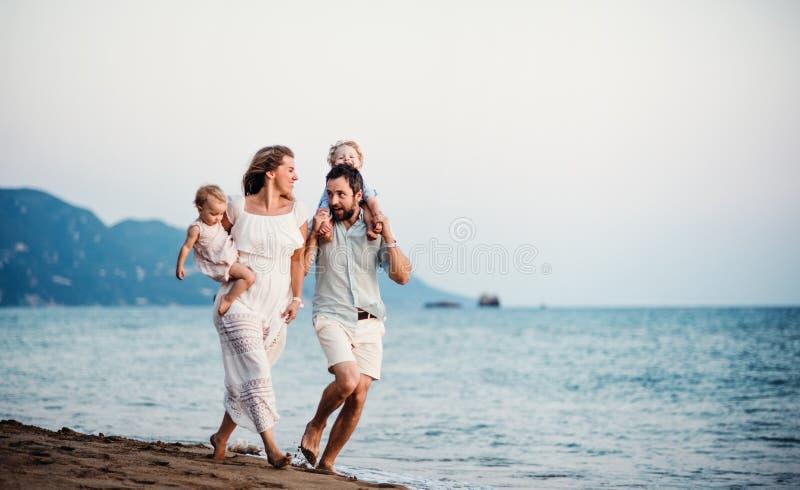 Junge Familie mit zwei Kleinkindkindern, die auf Strand an den Sommerferien gehen lizenzfreies stockfoto