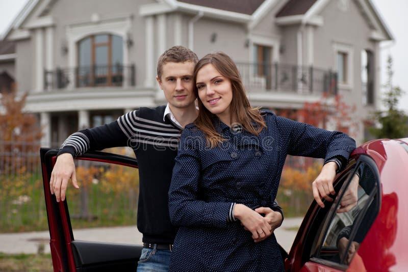 Junge Familie nahe Auto auf Hintergrundhaus lizenzfreies stockfoto