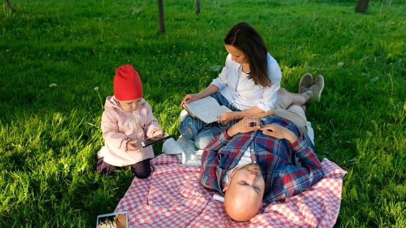 Junge Familie steht auf Natur, ein kleines Kind nimmt einen Smartphone in seinen Armen, die Mutter liest ein Buch, den Vater stil lizenzfreies stockbild