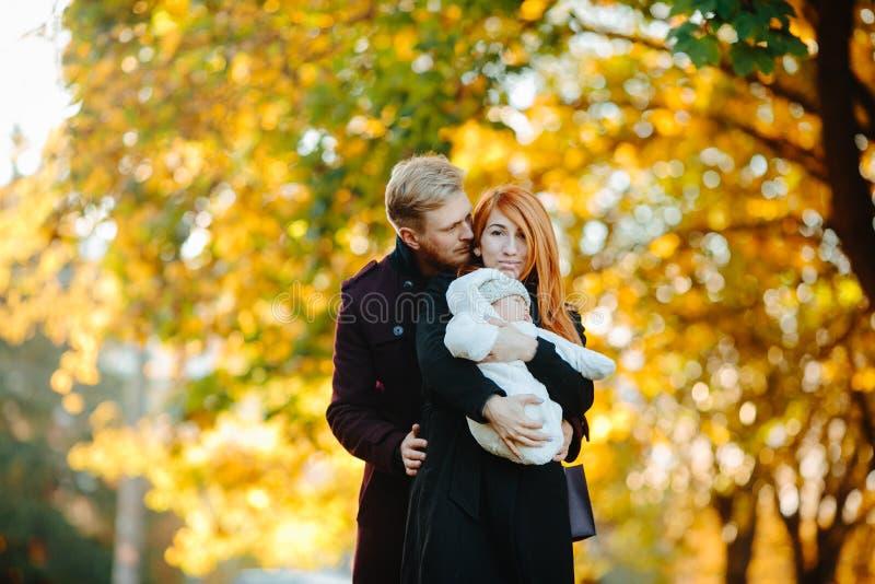 Junge Familie und neugeborener Sohn im Herbst parken lizenzfreie stockfotos
