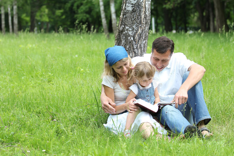 Junge Familie, welche die Bibel liest stockfotografie