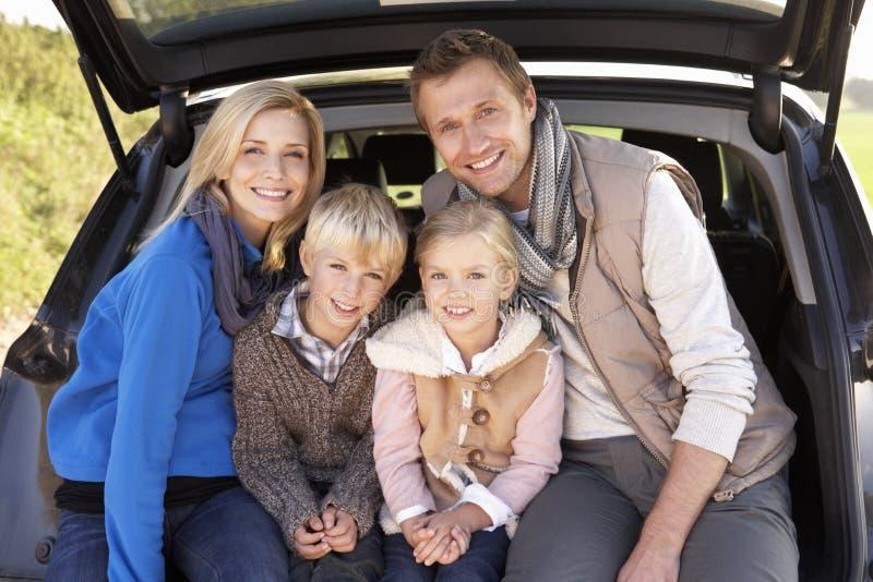 Junge Familienhaltung zusammen an der Rückseite des Autos stockfotos