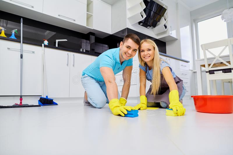 Junge Familienpaare, die Reinigung in der Küche tun stockfotografie